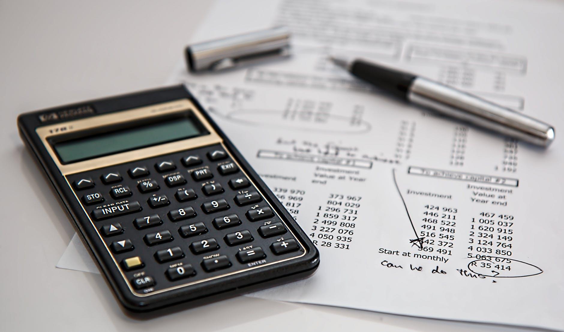 black calculator near ballpoint pen on white printed paper