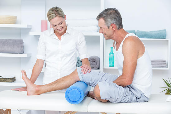 Doctor examining her patient leg in medical office-1