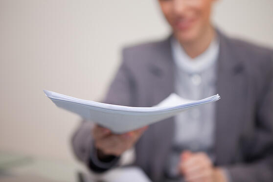 Paperwork being handed over by young businesswoman