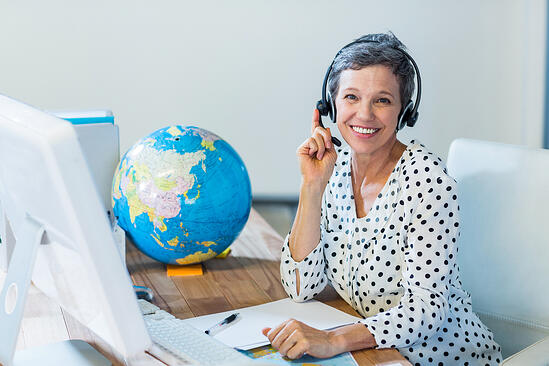Smiling travel agent sitting at her desk in the office-1