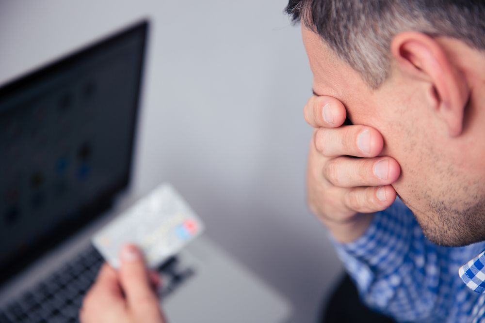 Upset man holding credit card with laptop on background-1