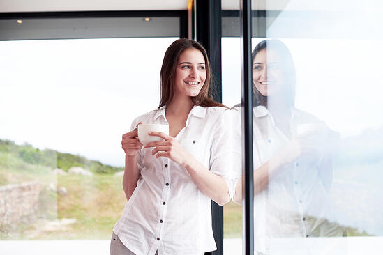 beautiful young woman drink first morning coffee at modern home interior with rain drops on big window door glass-1