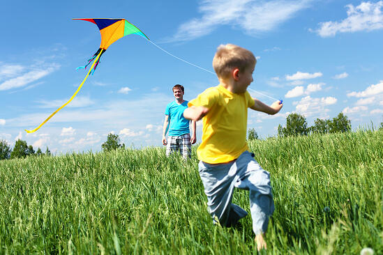father with son in summer playing with kite